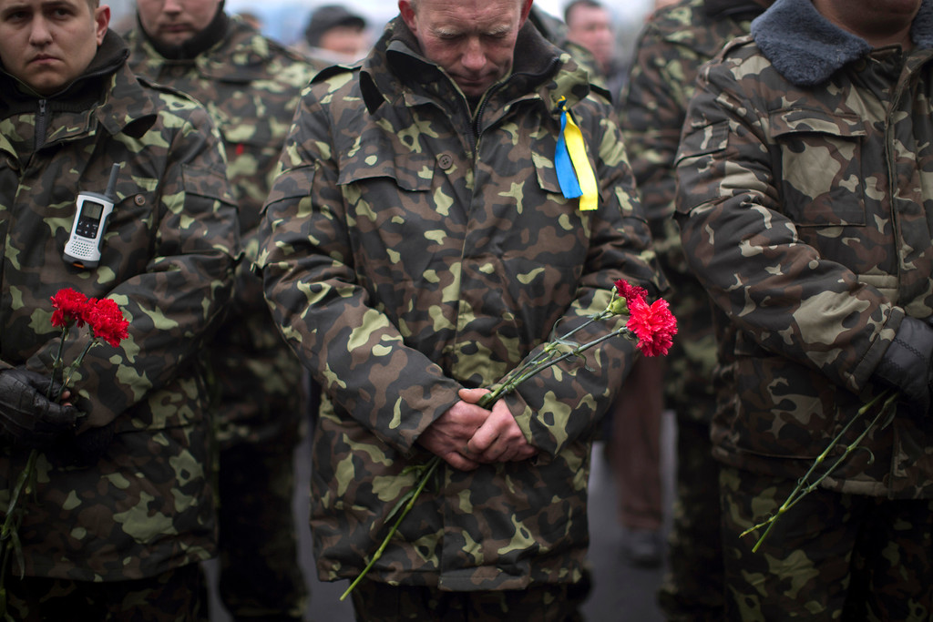 . Ukrainian men wearing camouflage uniforms holds a flowers during the funeral of Volodymyr Topiy, 59, who was found burned in the house of trade unions in Kiev\'s Independence Square during recent clashes with police, Ukraine, Tuesday, March 4, 2014. Vladimir Putin ordered tens of thousands of Russian troops participating in military exercises near Ukraine\'s border to return to their bases as U.S. Secretary of State John Kerry was on his way to Kiev. Tensions remained high in the strategic Ukrainian peninsula of Crimea with troops loyal to Moscow fired warning shots to ward off protesting Ukrainian soldiers. (AP Photo/Emilio Morenatti)