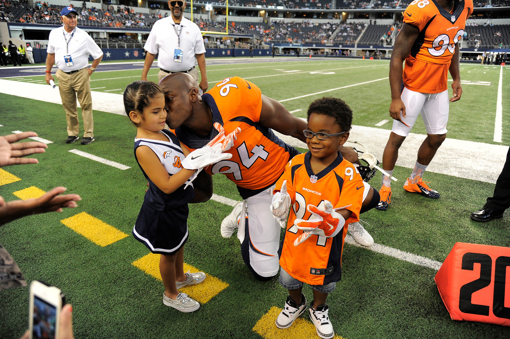. ARLINGTON, TX - AUGUST 28: Denver Broncos defensive end DeMarcus Ware (94) kisses his daughter Marley as DeMarcus Jr. shows off his gloves from Denver Broncos wide receiver Demaryius Thomas (88) before the game against the Dallas Cowboys August 28, 2014 at AT&T Stadium. (Photo by John Leyba/The Denver Post)