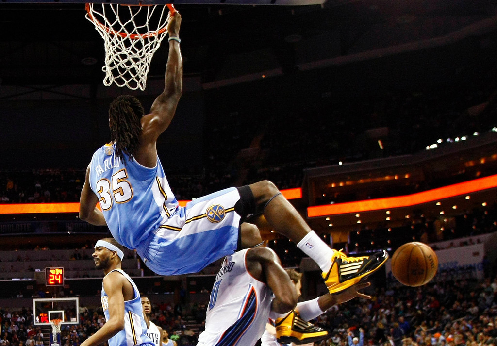 . Denver Nuggets small forward Kenneth Faried (35) hands on the rim after a dunk while Charlotte Bobcats power forward Bismack Biyombo (0) works to get out from under Faried during the second half of their NBA basketball game in Charlotte, North Carolina February 23, 2013. REUTERS/Chris Keane