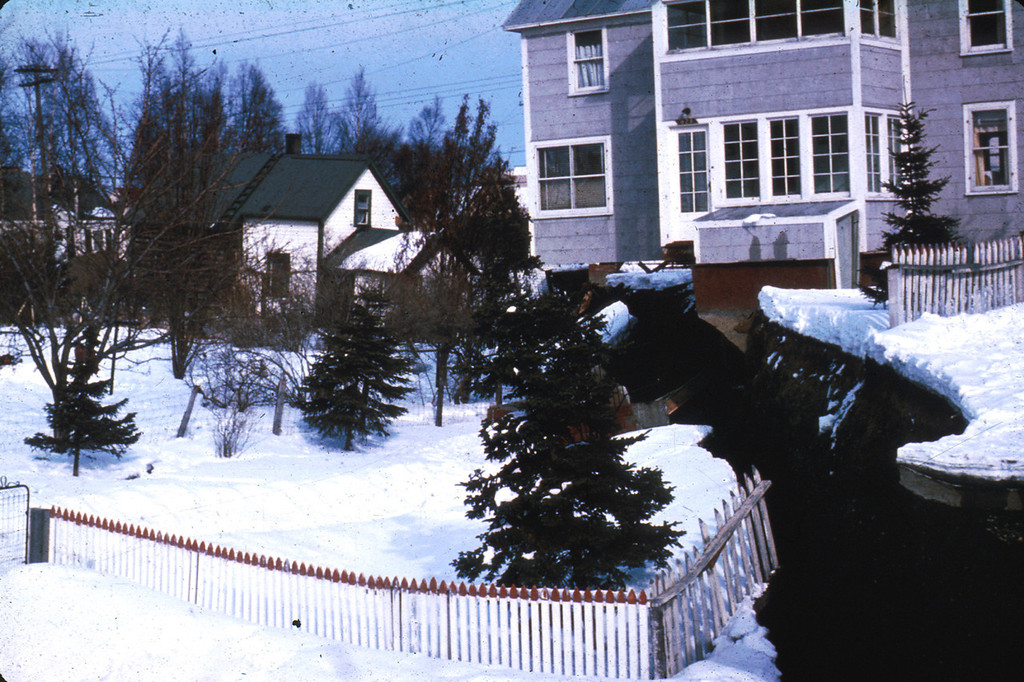 . Alaska Earthquake March 27, 1964. One of the scarps bounding the graben of the L Street landslide in Anchorage. The house was undercut by subsidence of the graben. U.S. Geological Survey photo