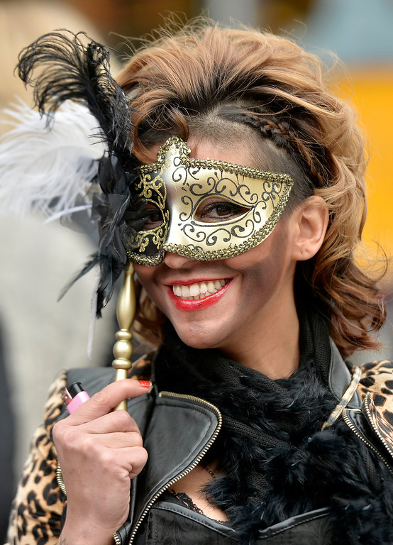 ". A woman smiles behind her mask when tens of thousands revelers dressed in carnival costumes celebrate the start of the street-carnival on the so called ""Old Women\'s Day\"" in the party capital Cologne, Germany, Thursday, Feb. 27, 2014. (AP Photo/Martin Meissner)"