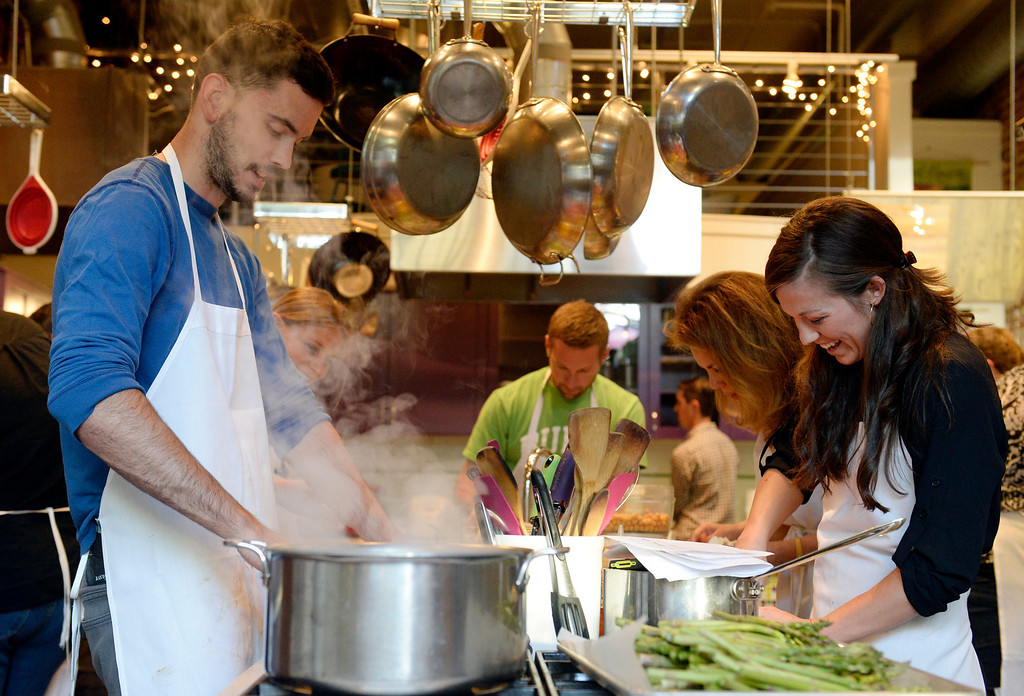 . DENVER, CO - JUNE 6:  Contestants left to right: Joseph Mackey, Tommy Ward, Donna Kanger-Trujillo and Kristin Petty  work together at their table as  the Stir Cooking School at 3215 Zuni Street in Denver, hosted an Iron Chef styled cooking event  on Friday, June 6, 2014.  The evening pitted three tables competing against one another.  (Denver Post Photo by Cyrus McCrimmon)