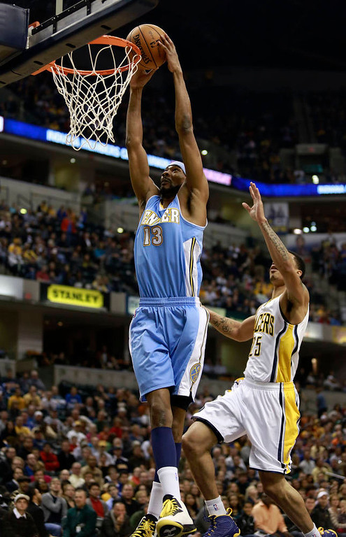 . Denver Nuggets forward Corey Brewer (13) dunks the basketball guarded by Indiana Pacers forward Gerald Green during the second quarter of an NBA basketball game in Indianapolis, Indiana December 7, 2012.  REUTERS/Brent Smith