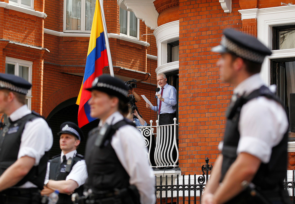 ". In this Aug. 19, 2012 file photo, surrounded by British police, WikiLeaks founder Julian Assange, center, makes a statement to the media and supporters from a window of the Ecuadorian Embassy in central London. Assange entered the embassy in June in an attempt to gain political asylum and prevent him from being extradited to Sweden, where he faces allegations of sex crimes, which he denies.  Assange called on United States President Barack Obama to \'end a ""witch hunt\"" against the secret-spilling WikiLeaks organization.  (AP Photo/Sang Tan, File)"
