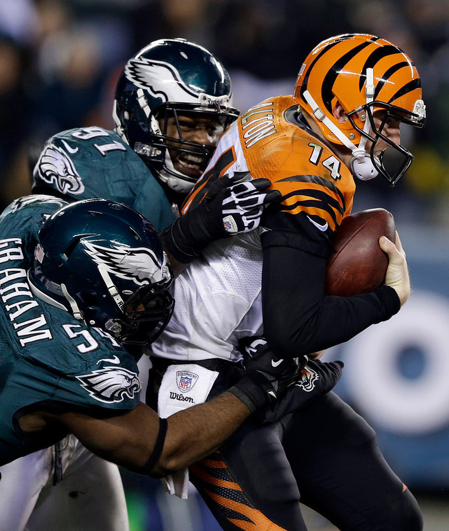 . Cincinnati Bengals\' Andy Dalton, right, is sacked by Philadelphia Eagles\' Brandon Graham, left, and Fletcher Cox in the second half of an NFL football game on Thursday, Dec. 13, 2012, in Philadelphia. (AP Photo/Matt Rourke)