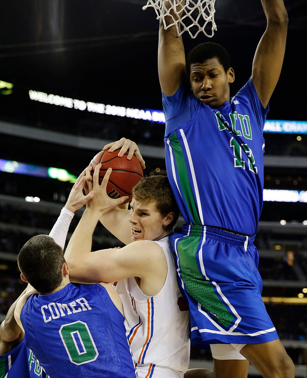 . Florida\'s Erik Murphy grabs a rebound as  Florida Gulf Coast\'s Eric McKnight (12) holds the rim and , Brett Comer (0) defends during the second half of a regional semifinal game in the NCAA college basketball tournament, Saturday, March 30, 2013, in Arlington, Texas. (AP Photo/David J. Phillip)