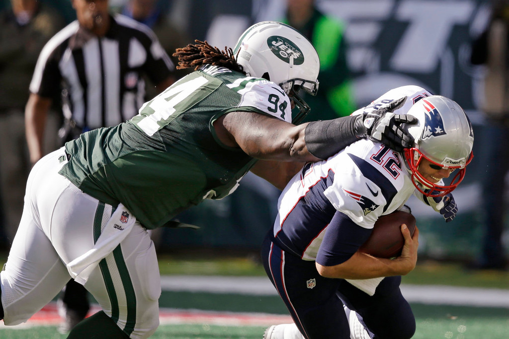 . New York Jets nose tackle Damon Harrison (94) sacks New England Patriots\' Tom Brady (12) during the second half of an NFL football game Sunday, Oct. 20, 2013, in East Rutherford, N.J.  (AP Photo/Seth Wenig)