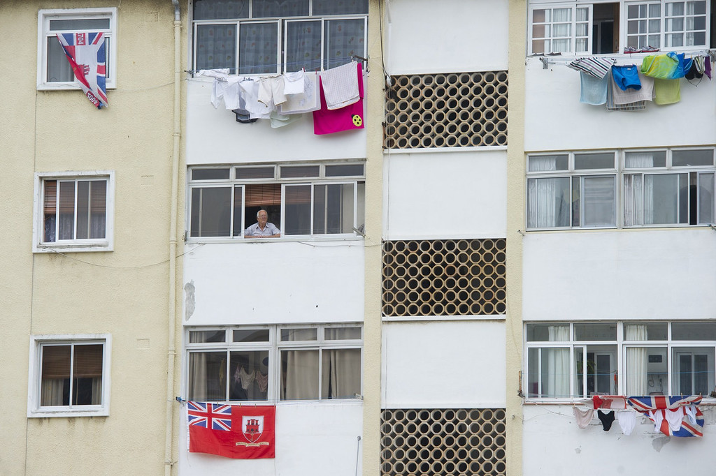 ". A man stands at a window above British flags in Gibraltar on August 13, 2013 as Spain enforced tight border checks in a growing row with Britain over the tiny territory and its surrounding waters. On the ""Rock\"" itself, defiant residents declared themselves thoroughly British, surrounded by English pubs serving fish and chips, Royal Mail letter boxes, bright red telephone cabins and the occasional monkey.   MARCOS MORENO/AFP/Getty Images"