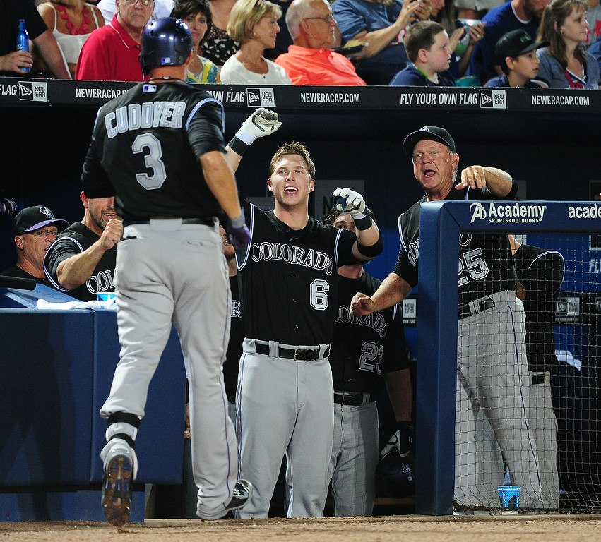 . ATLANTA, GA - MAY 23: Michael Cuddyer #3 of the Colorado Rockies is congratulated by Corey Dickerson #6 and Blake Doyle #25 after hitting a 6th inning solo home run against the Atlanta Braves at Turner Field on May 23, 2014 in Atlanta, Georgia. (Photo by Scott Cunningham/Getty Images)