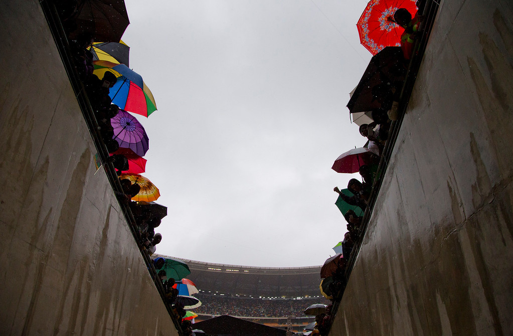 . People look into a tunnel as they wait for the arrival of President Barack Obama during the memorial service for former South African president Nelson Mandela at the FNB Stadium in Soweto near Johannesburg, Tuesday, Dec. 10, 2013. World leaders, celebrities, and citizens from all walks of life gathered on Tuesday to pay respects during a memorial service for the former South African president and anti-apartheid icon. (AP Photo/Evan Vucci)