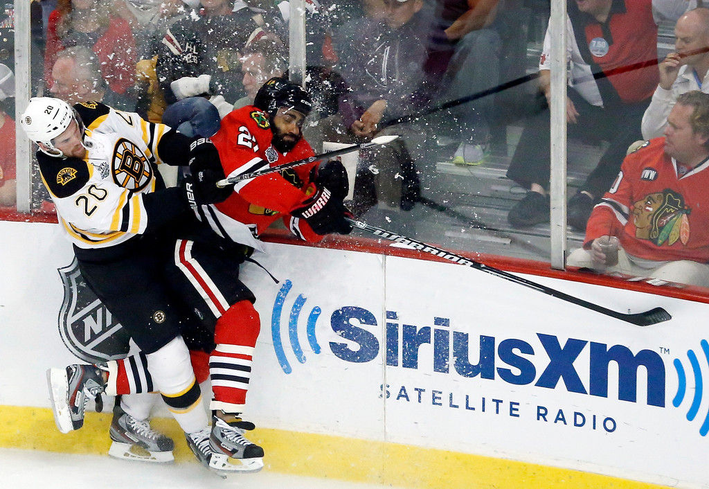 . Boston Bruins left wing Daniel Paille (20) and Chicago Blackhawks defenseman Johnny Oduya (27) collide during the first period of Game 1 in their NHL Stanley Cup Final hockey series on Wednesday, June 12, 2013, in Chicago. (AP Photo/Charles Rex Arbogast)