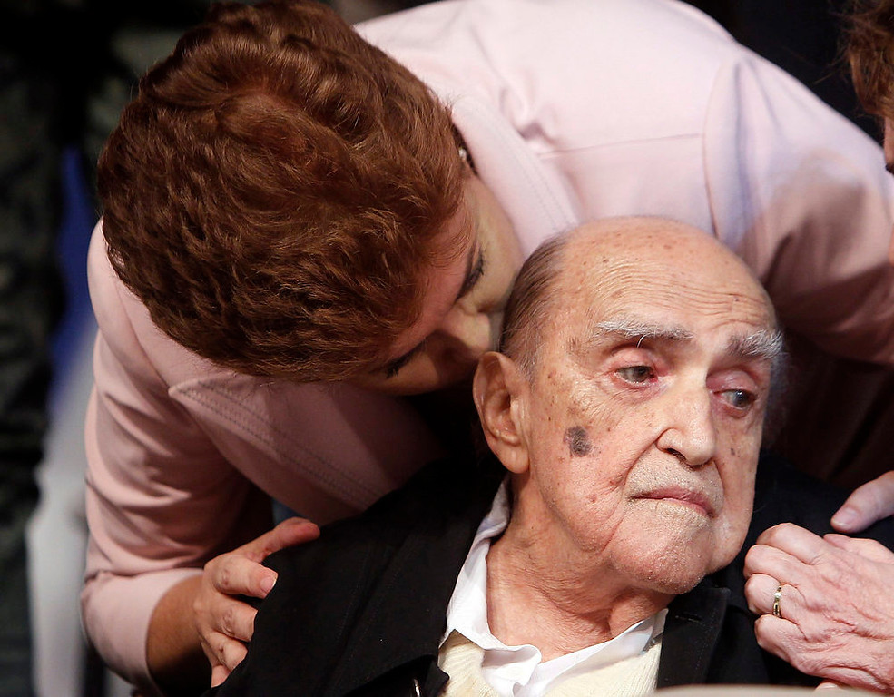 . Brazil\'s President Dilma Roussef kisses Brazilian architect Oscar Niemeyer during a meeting with artists and intellectuals when Rousseff was still a presidential candidate, in Rio de Janeiro, in this October 18, 2010 photo. Niemeyer, a towering patriarch of modern architecture who shaped the look of modern Brazil and whose inventive, curved designs left their mark on cities worldwide, died late on December 5, 2012. He was 104. Niemeyer had been battling kidney ailments and pneumonia for nearly a month in a Rio de Janeiro hospital. His death was confirmed by a hospital spokesperson. REUTERS/Bruno Domingos