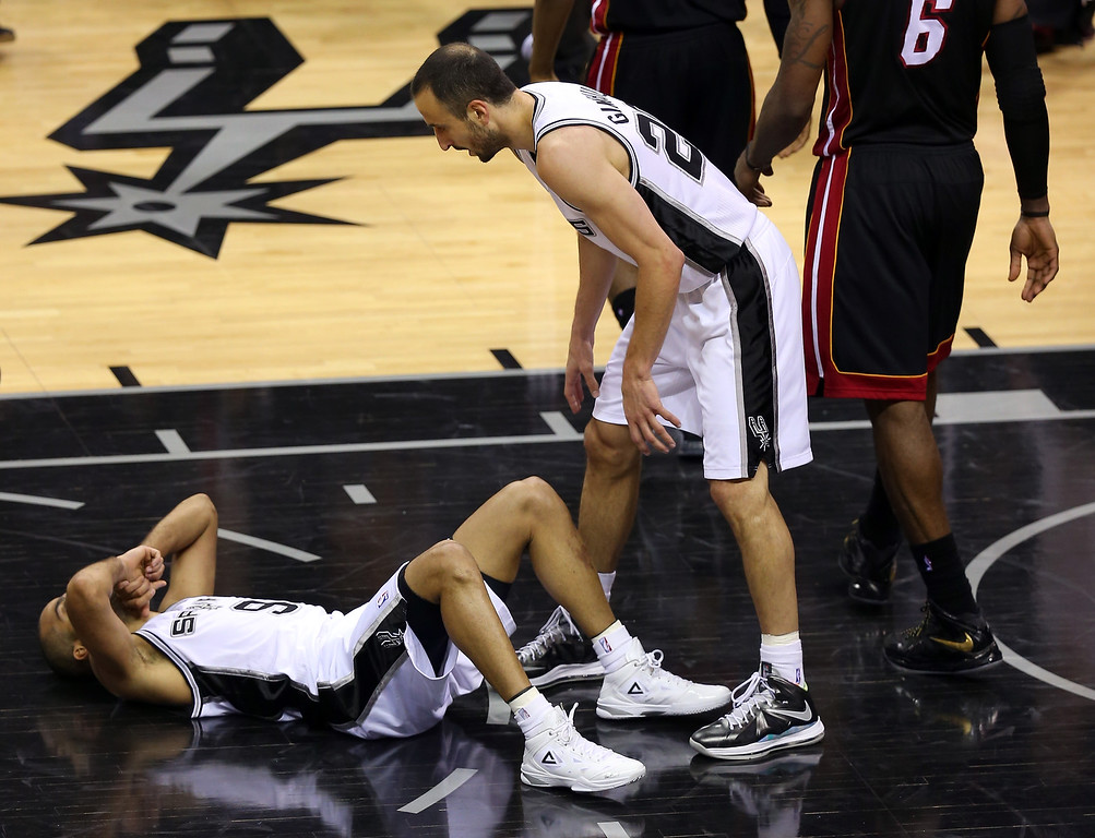 . Tony Parker #9 lays on the court as Manu Ginobili #20 of the San Antonio Spurs looks down at him in the fourth quarter against the Miami Heat during Game Four of the 2013 NBA Finals at the AT&T Center on June 13, 2013 in San Antonio, Texas.   (Photo by Mike Ehrmann/Getty Images)