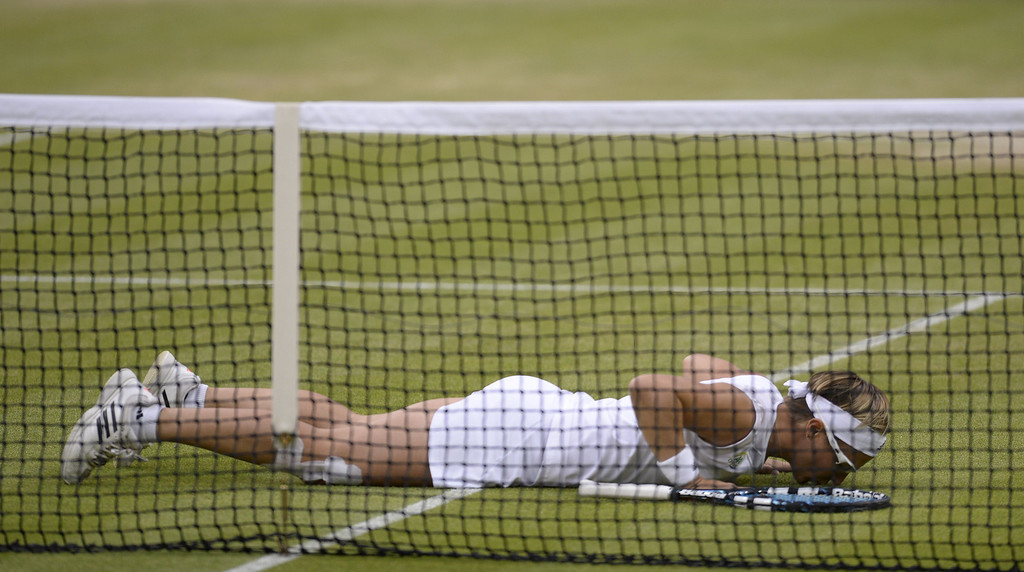 . Belgium\'s Kirsten Flipkens kisses the ground after beating Czech Republic\'s Petra Kvitova during their women\'s singles quarter-final match on day eight of the 2013 Wimbledon Championships tennis tournament at the All England Club in Wimbledon, southwest London, on July 2, 2013. Flipkens won 4-6, 6-3, 6-4. ADRIAN DENNIS/AFP/Getty Images