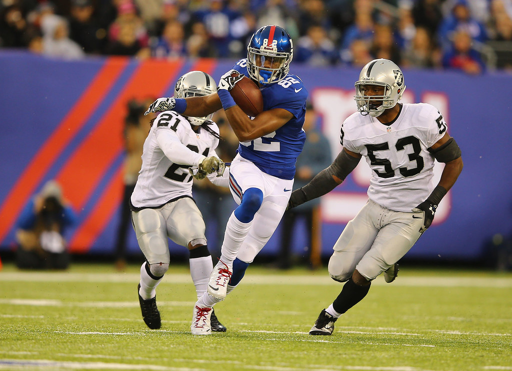 . Rueben Randle #82 of the New York Giants runs after a catch as  Mike Jenkins #21, and  Nick Roach #53 of the Oakland Raiders give chase  during their game at MetLife Stadium on November 10, 2013 in East Rutherford, New Jersey.  (Photo by Al Bello/Getty Images)