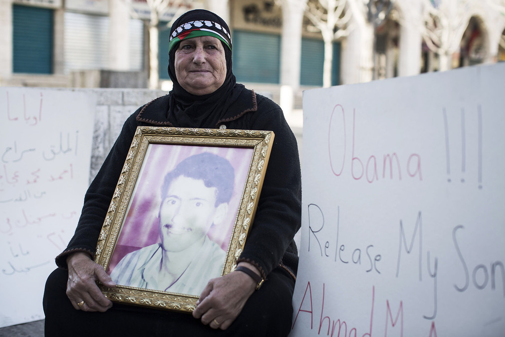 . A Palestinian woman holding a photograph sits in protest outside the church of nativity before the official visit of U.S. President Barack Obama on March 22, 2013 in Bethlehem, West Bank.  (Photo by Ilia Yefimovich/Getty images)