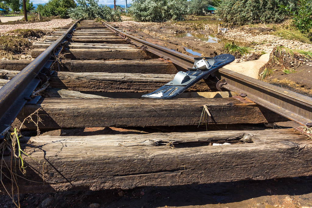 . A snowboard rests discarded on railway tracks in Longmont near 3rd Avenue and Hover Street. St. Vrain Creek to the left of the tracks (not visible) washed much of the ballast away from the tracks leaving exposed sleepers. The force of the water was able to warp the tracks. Photo by Arien Talabac