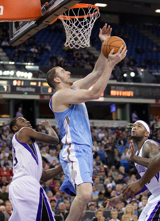 . Denver Nuggets center Kosta Koufos, center, goes to the basket between Sacramento Kings\' Tyreke Evans, left, and DeMarcus Cousins during the first quarter of an NBA basketball game in Sacramento, Calif., Tuesday, March 5, 2013. (AP Photo/Rich Pedroncelli)