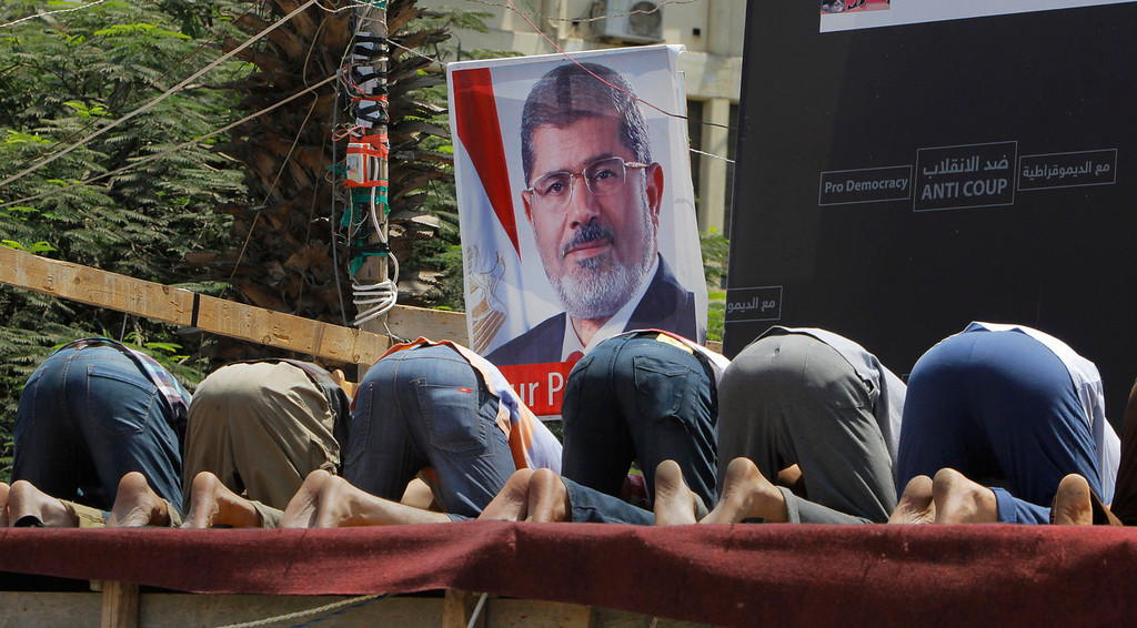 """. Supporters of Egypt\'s ousted President Mohammed Morsi pray in front of his poster in Nahda Square, where protesters have installed their camp near Cairo University in Giza, southwestern Cairo, Egypt, Monday, Aug. 12, 2013. Egyptian authorities on Monday postponed a move to disperse two Cairo sit-ins by supporters of the country\'s ousted president to \""""avoid bloodshed,\"""" an official said, as Islamist supporters stepped up rallies to demand his return to power. (AP Photo/Amr Nabil)"""
