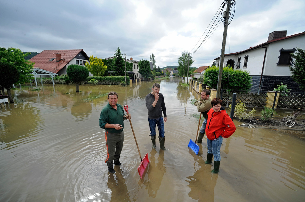 . People stand on a flooded street along the White Elster in Wuenschendorf, Germany, on June 4, 2013. Photo. Chancellor Angela Merkel pledged 100 million euros ($130 million) in emergency aid for flood-ravaged areas on Tuesday, as surging waters that have claimed at least 11 lives and forced tens of thousands of evacuations across Europe bore down on Germany.   JENS-ULRICH KOCH/AFP/Getty Images