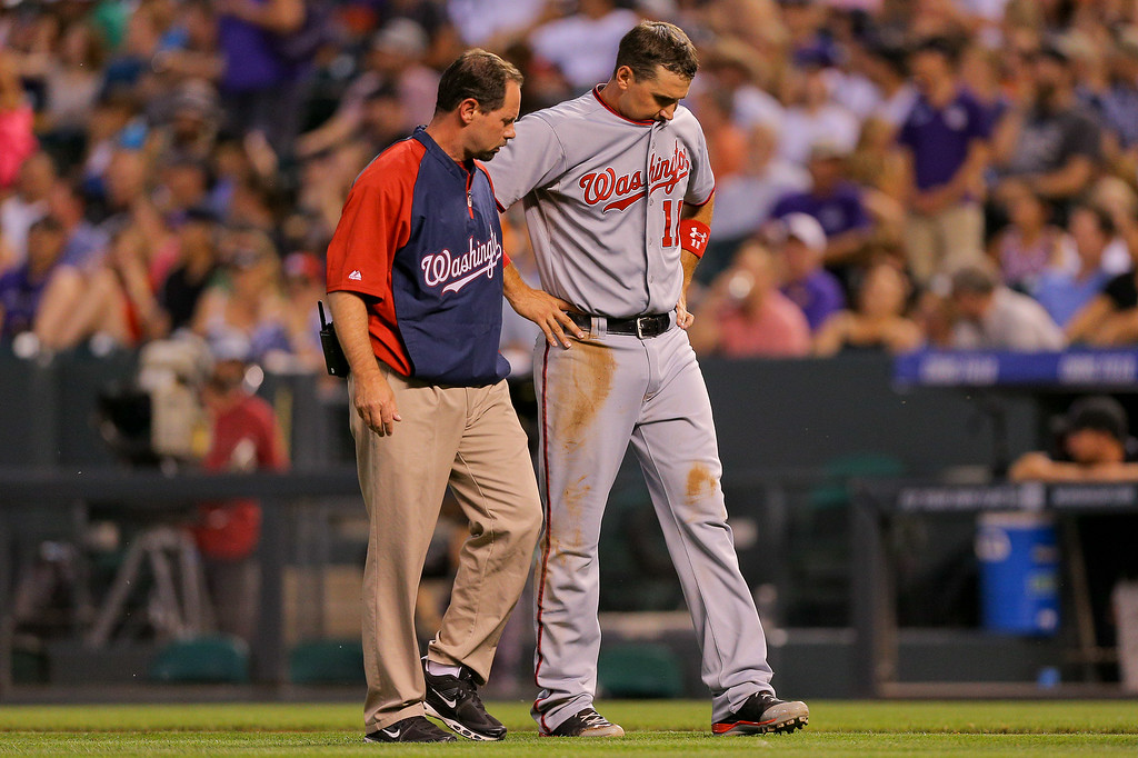 . DENVER, CO - JULY 22:  Ryan Zimmerman #11 of the Washington Nationals walks off the field under the supervision of the training staff after injuring himself running to first base during the sixth inning against the Colorado Rockies at Coors Field on July 22, 2014 in Denver, Colorado.  Zimmerman was removed from the game. (Photo by Justin Edmonds/Getty Images)