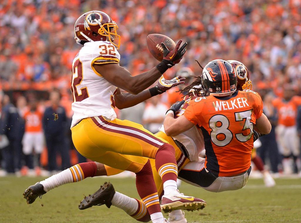 . Washington Redskins defensive back Jordan Pugh (32) intercepts a pass as Denver Broncos wide receiver Wes Welker (83) is tackled in the fourth quarter.   (Photo by John Leyba/The Denver Post)