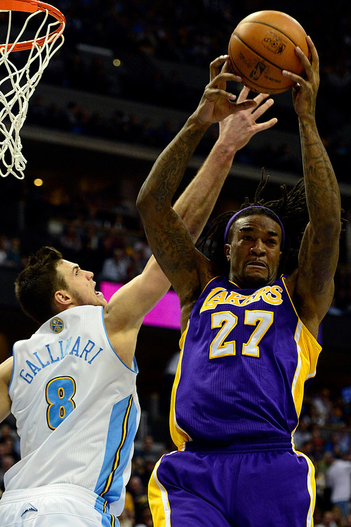 . Los Angeles Lakers center Jordan Hill (27) grabs a rebound away from Denver Nuggets small forward Danilo Gallinari (8) during the second half of the Nuggets\' 126-114 win at the Pepsi Center on Wednesday, December 26, 2012. AAron Ontiveroz, The Denver Post