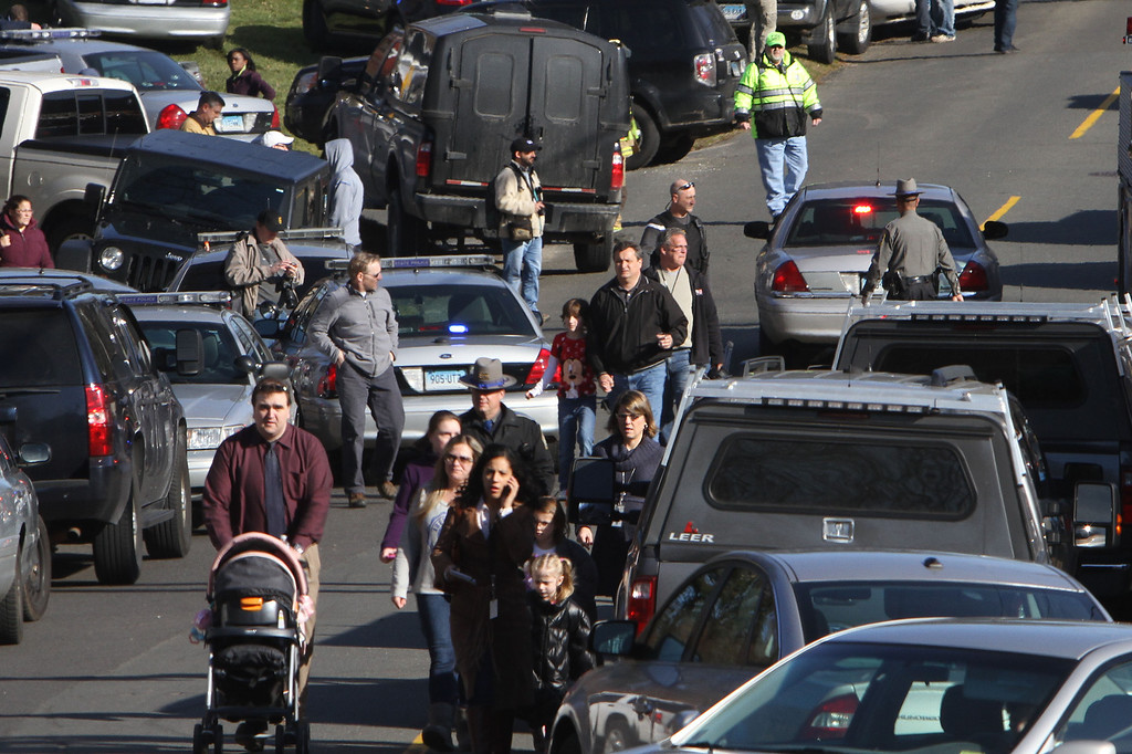 . Parents walk away from the Sandy Hook School with their children following a shooting at the school Friday, Dec. 14, 2012 in Newtown, Conn. A man opened fire inside the Connecticut elementary school where his mother worked Friday, killing 26 people, including 18 children, and forcing students to cower in classrooms and then flee with the help of teachers and police. (AP Photo/The Journal News, Frank Becerra Jr.)