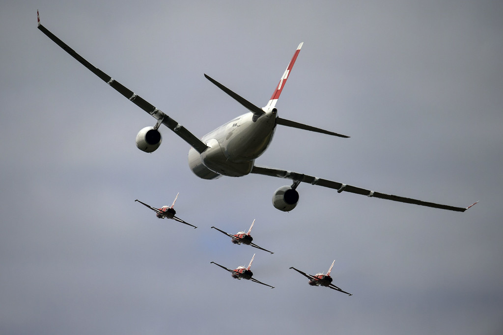 """. An Airbus A330 commercial plane of Swiss International Air Lines flies with fighter jets of the \""""Patrouille Suisse\"""" (Swiss patrol) on August 30, 2014 during the first day of AIR14 air show in Payerne, western Switzerland.  AFP PHOTO / FABRICE COFFRINI/AFP/Getty Images"""