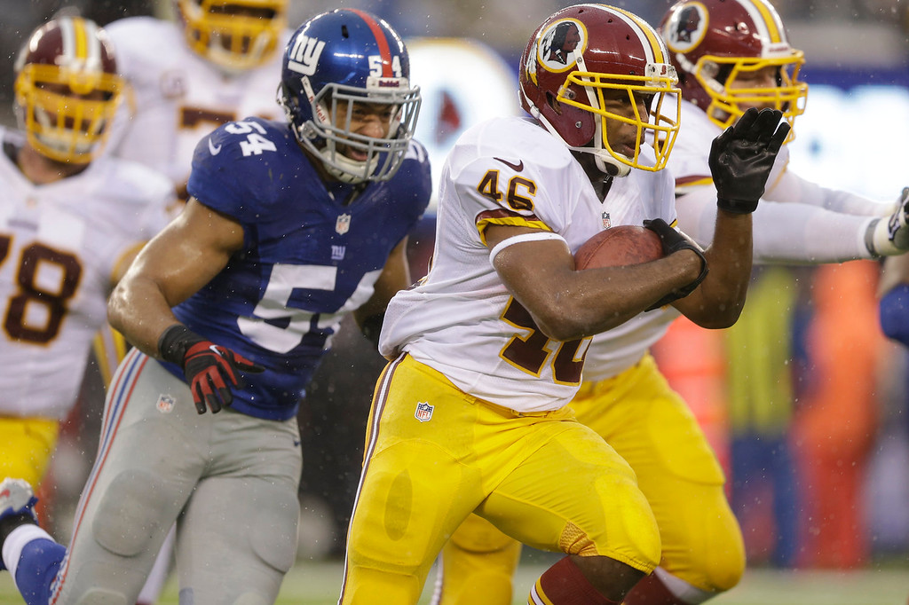 . Washington Redskins running back Alfred Morris (46) runs past New York Giants\' Spencer Paysinger (54) during the first half of an NFL football game on Sunday, Dec. 29, 2013, in East Rutherford, N.J. (AP Photo/Julio Cortez)