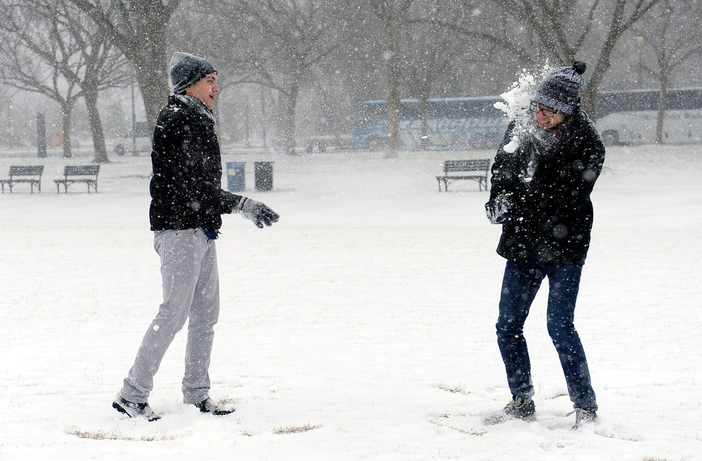. Rick Mendenhall of Albuquerque, N.M., right, gets hit in the face during a snowball fight with his friend Jeff Scott of Los Angeles, left, on the National Mall in Washington during the start of a major snowstorm, Tuesday, Jan. 21, 2014. (AP Photo/Susan Walsh)