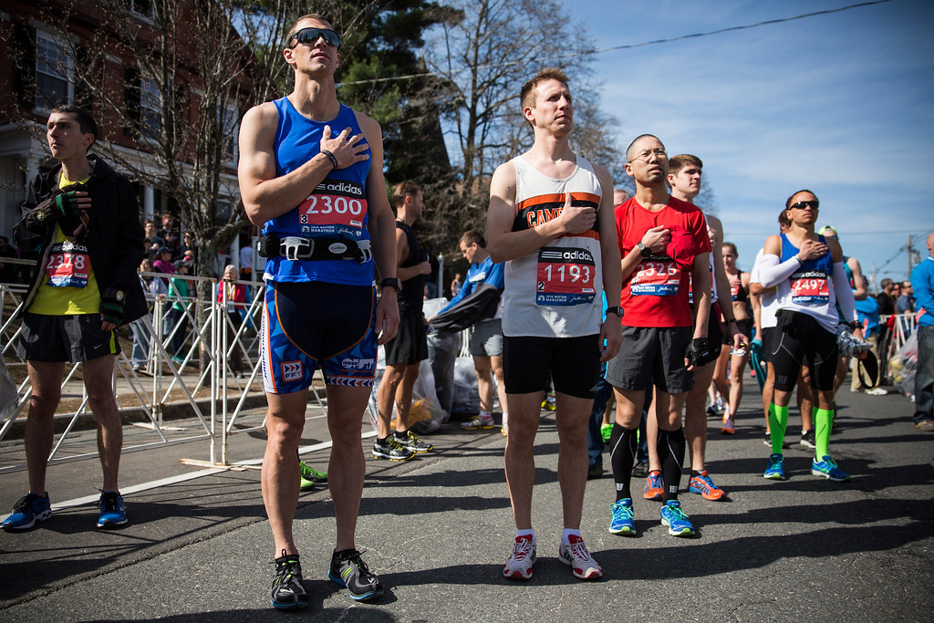 . Runners place their hands over their hearts during a singing of the National Anthem at the beginning of the Boston Marathon on April 21, 2014 in Hopkington, Massachusetts. Today marks the 118th Boston Marathon; security presence has been increased this year, due to two bombs that were detonated at the finish line last year, killing three people and injuring more than 260 others.  (Photo by Andrew Burton/Getty Images)