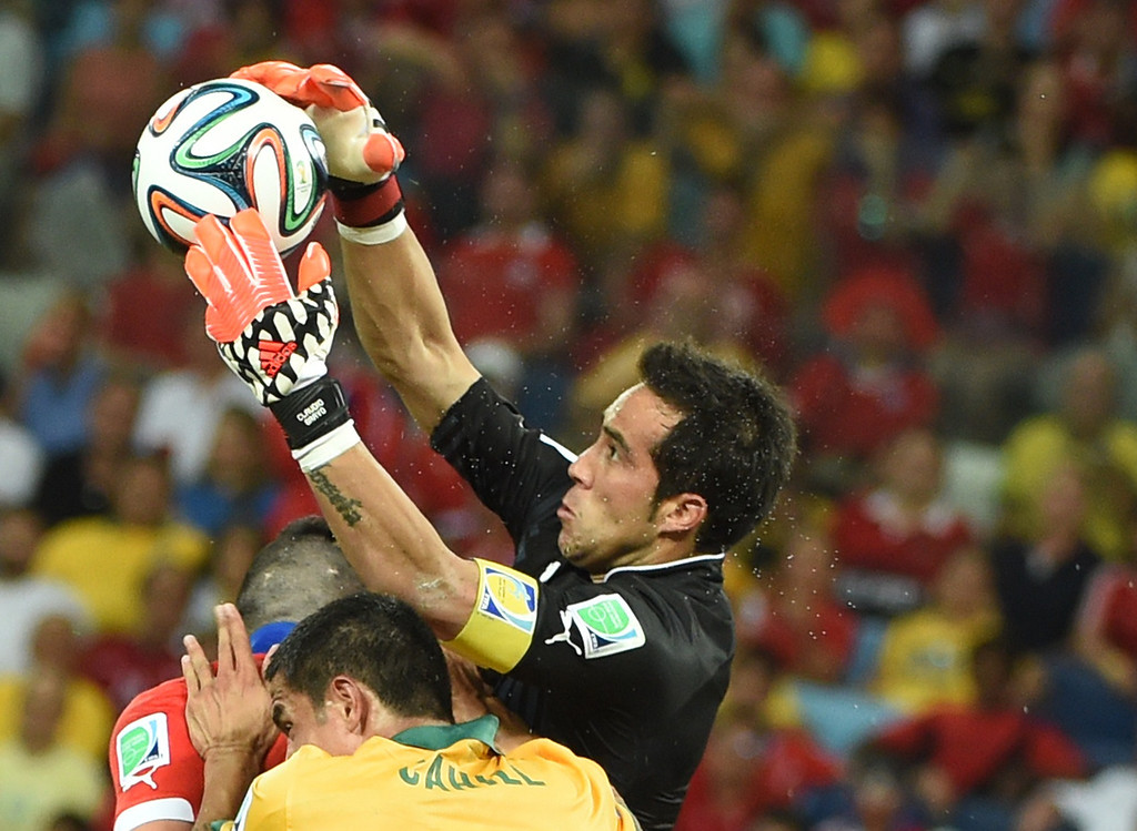 . Chile\'s goalkeeper Claudio Bravo saves the ball during a Group B football match between Chile and Australia at the Pantanal Arena in Cuiaba during the 2014 FIFA World Cup on June 13, 2014.     AFP PHOTO / WILLIAM WEST