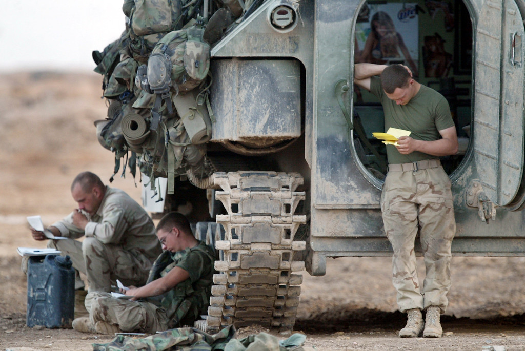 . U.S. Marines from Task Force Tarawa 1/2 Charlie Company read letters that arrived in the mail from home April 14, 2003 near Al Kut, Iraq. (Photo by Joe Raedle/Getty Images)