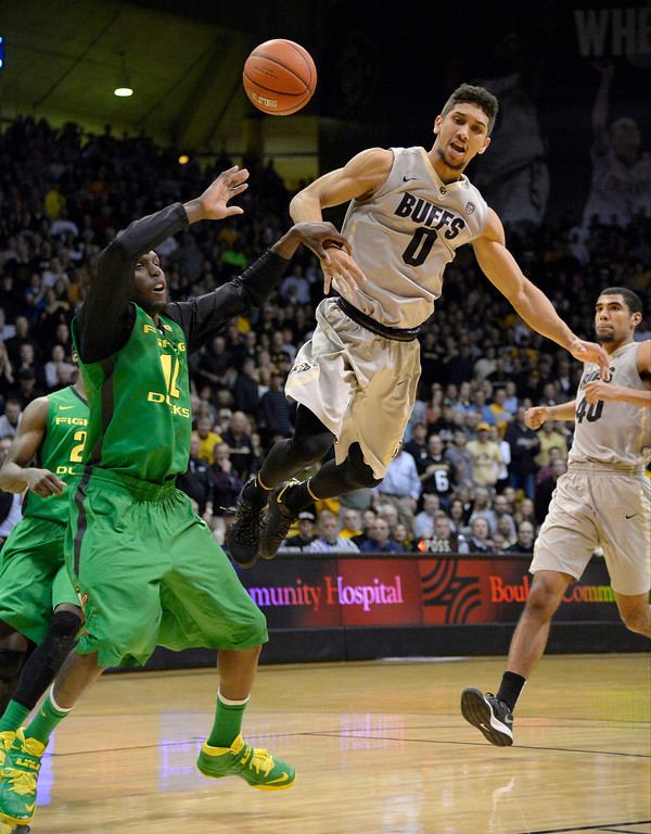 . Colorado Buffaloes guard Askia Booker (0) gets fouled by Oregon Ducks guard Jason Calliste (12) during the second half January 5, 2014 at Coors Events Center. The Colorado Buffaloes defeated the Oregon Ducks 100-91. (Photo by John Leyba/The Denver Post)