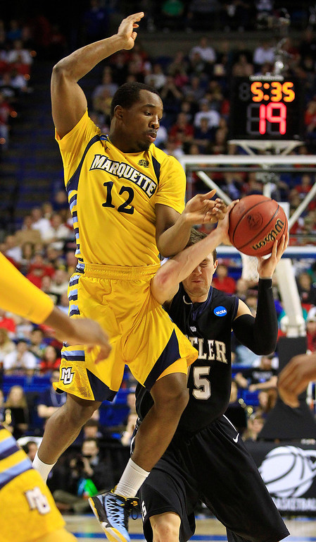 . Butler guard Rotnei Clarke (15) shoots against Marquette guard Derrick Wilson (12) in the first half of a third-round NCAA college basketball tournament game on Saturday, March 23, 2013, in Lexington, Ky. (AP Photo/James Crisp)