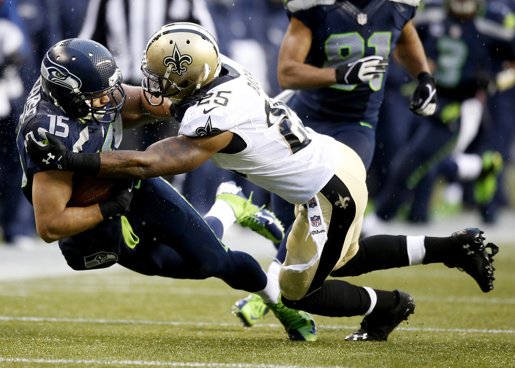 . SEATTLE, WA - JANUARY 11:  Wide receiver Jermaine Kearse #15 of the Seattle Seahawks is tackled by free safety Rafael Bush #25 of the New Orleans Saints in the second quarter during the NFC Divisional Playoff Game at CenturyLink Field on January 11, 2014 in Seattle, Washington.  (Photo by Otto Greule Jr/Getty Images)