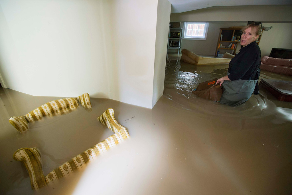. Lynn Sparks drags her possessions out of her flooded basement in the Elbow Park area of Calgary, Alberta June 22, 2013. Southern Alberta braced for more disruption on Saturday from floods that have killed at least two people, forced about 100,000 people from their homes and blacked out the center of Canada\'s oil capital, Calgary. Communities to the south and east of Calgary were put on high alert as the flood waters moved across the region. But with rainfall easing up, authorities were hopeful that the worst might now be over.  REUTERS/Todd Korol