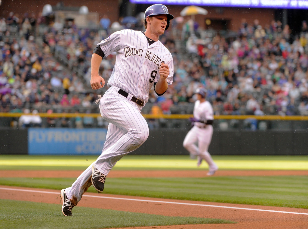 . DENVER, CO. - AUGUST 09: Colorado baserunner DJ LeMahieu scored and Troy Tulowitzki advanced to third on a single by batter Michael Cuddyer in the first inning. The Colorado Rockies hosted the Pittsburgh Pirates Friday night, August 9, 2013. Photo By Karl Gehring/The Denver Post