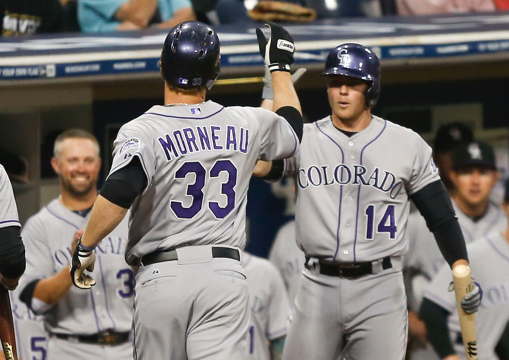 . Colorado Rockies\' Justin Morneau is greeted by Josh Rutledge, right, and Michael Cuddyer, left, after hitting a solo home run against the San Diego Padres in the second inning of a baseball game Wednesday, April 16, 2014, in San Diego.  (AP Photo/Lenny Ignelzi)