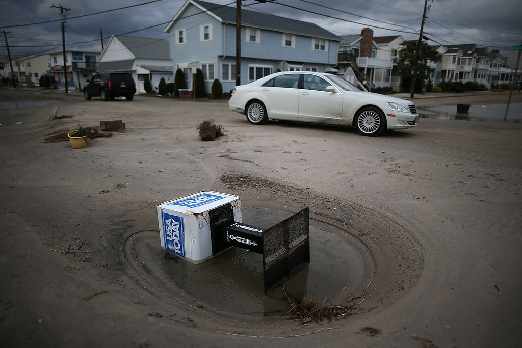 . A newspaper dispenser sits on a sand covered road, on October 30, 2012 in Ocean City, New Jersey. Hurricane Sandy made landfall last night on the New Jersey coastline bringing heavy winds and record floodwaters.  (Photo by Mark Wilson/Getty Images)