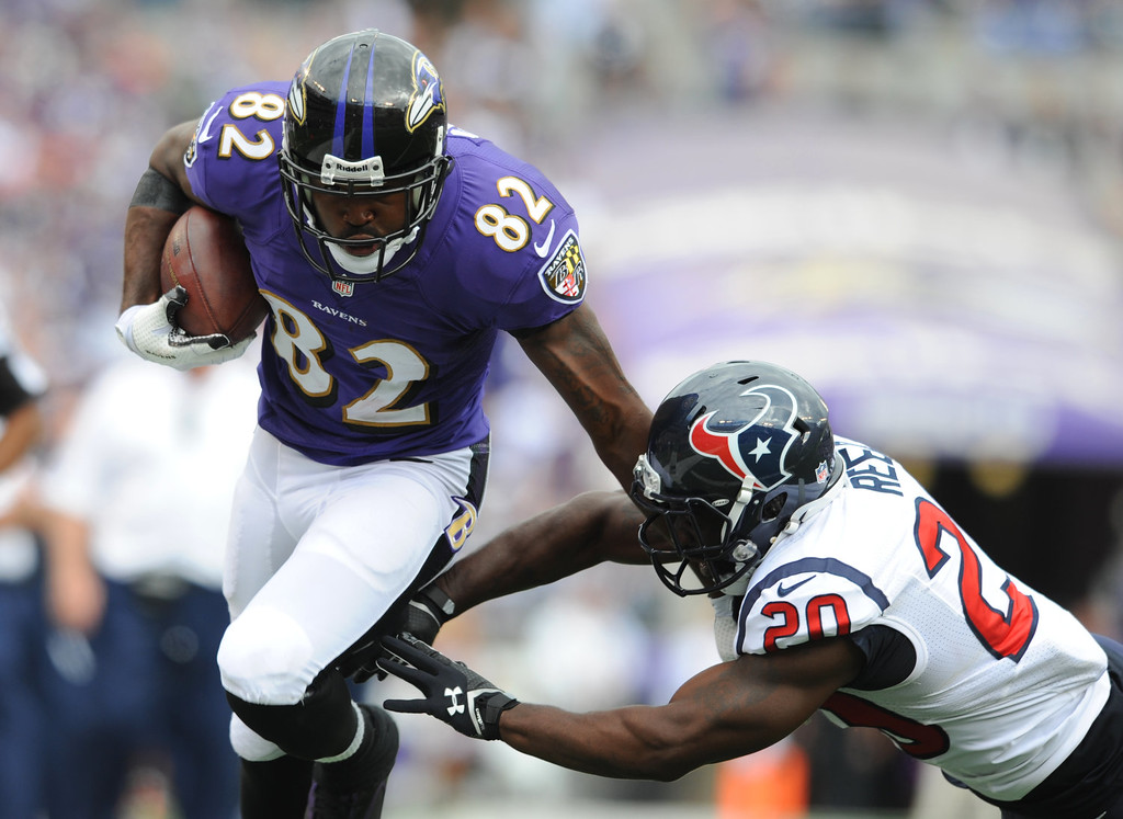 . Baltimore Ravens wide receiver Torrey Smith, left, rushes past Houston Texans free safety Ed Reed in the second half of an NFL football game Sunday, Sept. 22, 2013, in Baltimore. (AP Photo/Gail Burton)