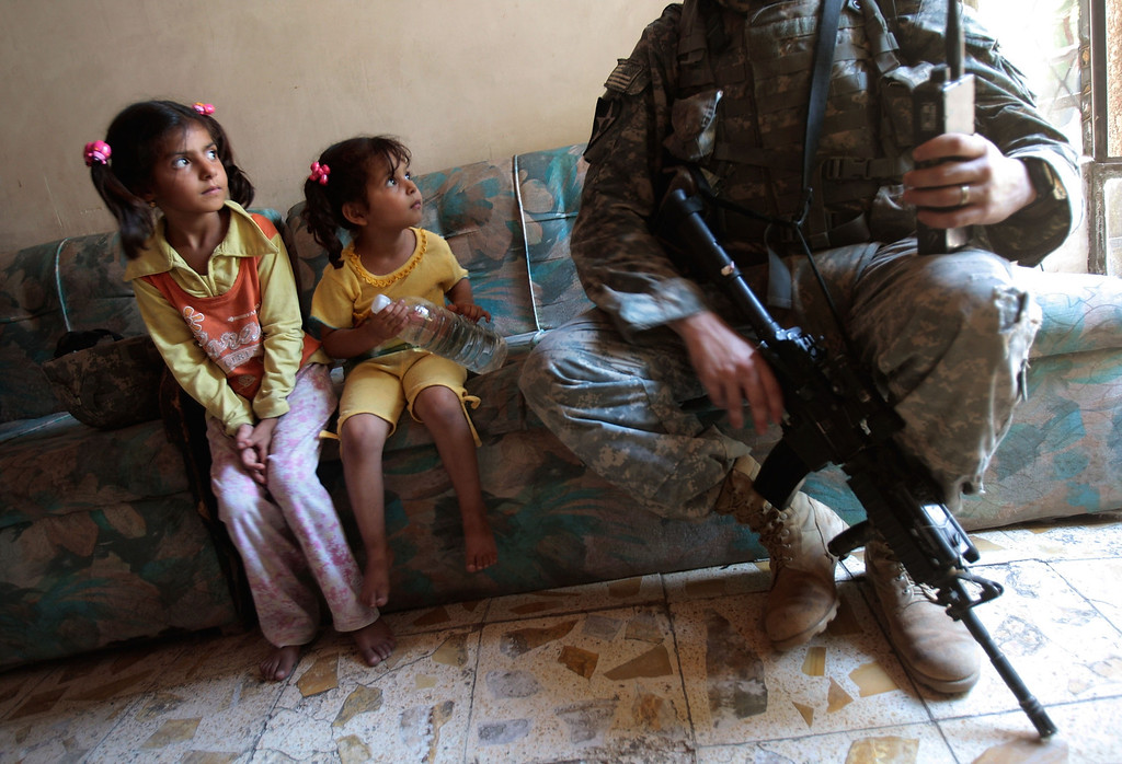 . Two Iraqi girls watch Staff Sgt. Nick Gibson of the 2nd Battalion, 12th Infantry Regiment of the 2nd Infantry Division June 21, 2007 as the unit was canvassing the tense Dora neighborhood of Baghdad, Iraq.  U.S. soldiers patrolled the area almost daily in an effort to get to know the residents and find insurgents.  (Photo by Chris Hondros/Getty Images)