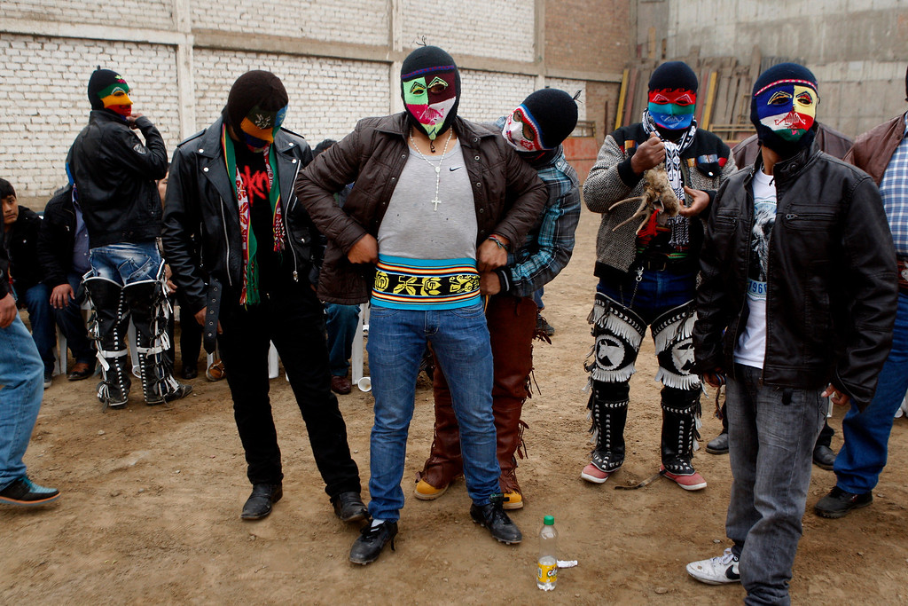 """. Masked fighter Eber Sabina, center, is helped by friends with his outfit before entering a Takanakuy ritual fight in Lima, Peru. The fighters dress up in costumes of Andean folklore figures, with the ski masks an integral part of the costume. Among the characters: \""""El Negro,\"""" representative of black slaves; \""""El Majeno,\"""" reminiscent of liquor salesmen from a region called Majes; and \""""El Gallo,\"""" the rooster. (AP Photo/Karel Navarro)"""