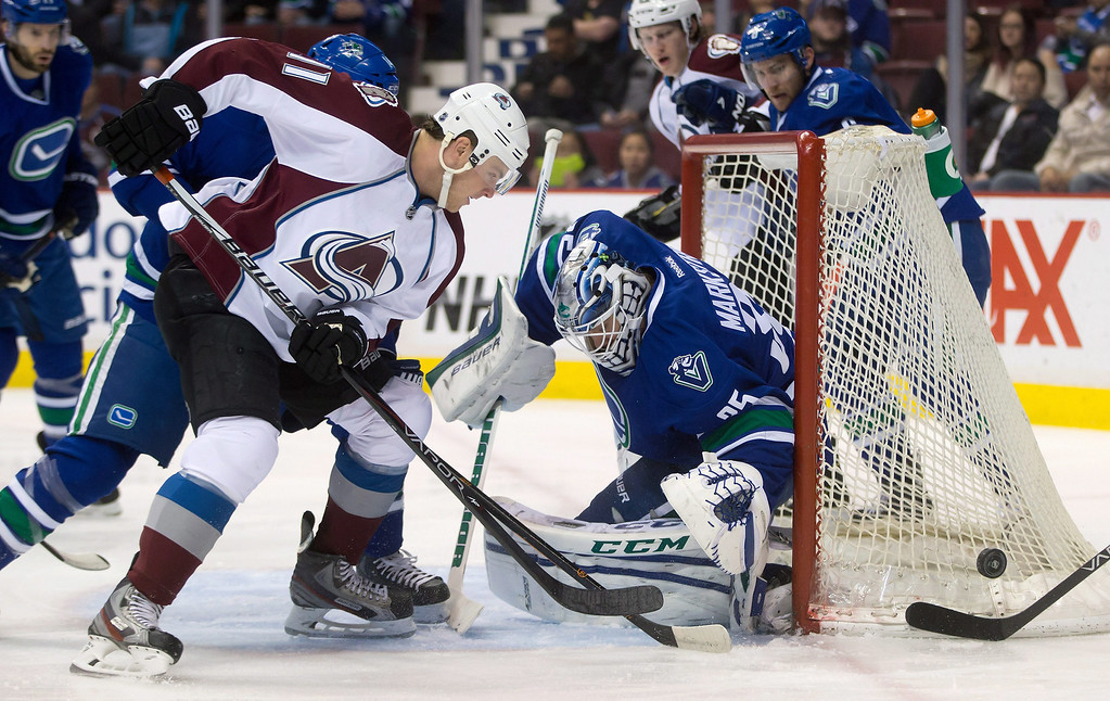 . Colorado Avalanche\'s Jamie McGinn, left, is stopped by Vancouver Canucks goalie Jacob Markstrom, of Sweden, during the first period of an NHL hockey game Thursday, April 10, 2014, in Vancouver, British Columbia. (AP Photo/The Canadian Press, Darryl Dyck)