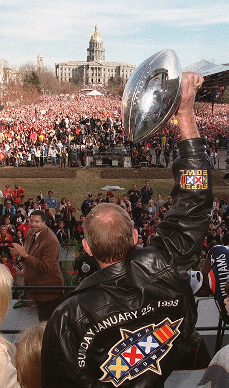 . Broncos owner Pat Bowlen holds up the Super Bowl trophy  to the crowd at Civic Center during a Rally for the World  Champions in 1998.  Kent Meireis, The Denver Post