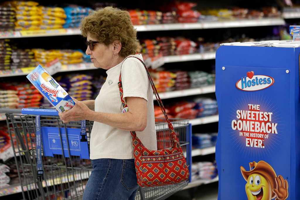 . In this Friday, July 12, 2013, file photo Jo Mullen picks up a box of Twinkies at Wal-Mart, in Bristol, Pa. The new owners of Hostess have leaner operating costs now that they\'re no longer using unionized workers. It turns out the spongy yellow cakes may also be a little smaller than the last Twinkies people remember eating.  (AP Photo/Matt Rourke)