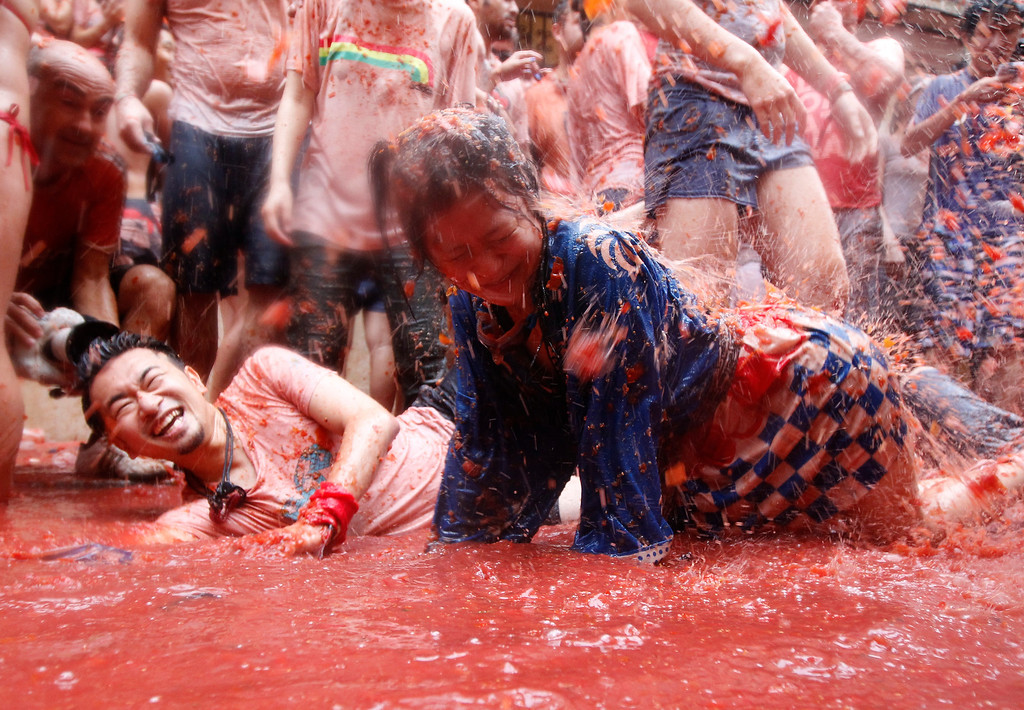 """. People lay on a puddle of tomato juice during the annual \""""tomatina\"""" tomato fight fiesta in the village of Bunol, 50 kilometers outside Valencia, Spain, Wednesday, Aug. 28, 2013. Thousands of people are splattering each other with tons of tomatoes in the annual \""""Tomatina\"""" battle in recession-hit Spain, with the debt-burdened town charging participants entry fees this year for the first time. Bunol town says some 20,000 people are taking part in Wednesday\'s hour-long street bash, inspired by a food fight among kids back in 1945. Participants were this year charged some 10 euros ($13) to foot the cost of the festival. Residents do not pay. (AP Photo/Alberto Saiz)"""