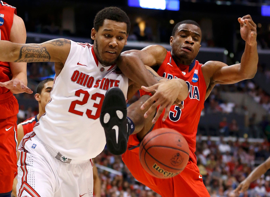 . Ohio State Buckeyes center Amir Williams (23) and Arizona Wildcats guard/forward Kevin Parrom (3) fight for a loose ball in the first half of their West Regional NCAA men\'s basketball game in Los Angeles, California March 28, 2013. REUTERS/Danny Moloshok
