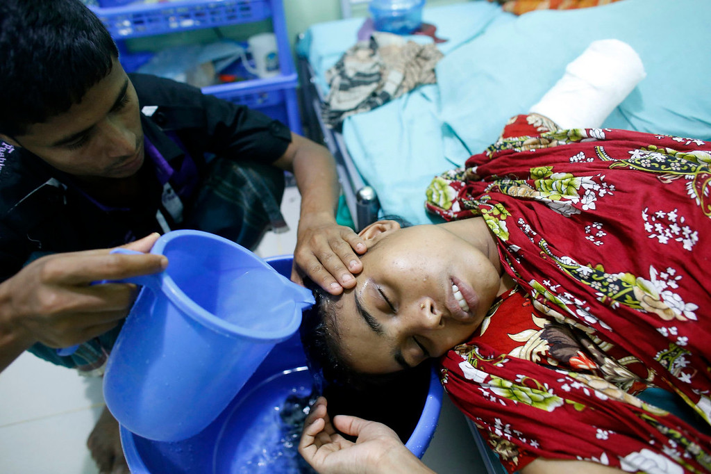 . A relative pours water on 25-year-old Rojina\'s head at the Centre for the Rehabilitation of the Paralysed (CRP) in Savar, Bangladesh June 4, 2013. Rescue workers, who pulled Rojina from the rubble of the collapsed Rana Plaza building, had to amputate part of her arm to rescue her. The April 24 collapse of the Rana Plaza complex, built on swampy ground outside Dhaka with several illegal floors, killed 1,132 workers and focused international attention on sometimes lax safety standards in Bangladesh\'s booming garment industry. At least five different Bangladesh agencies have dispatched teams to start inspecting the countryís thousands of garment factories, but there has been little coordination between them. More than four million people, mostly women, work in Bangladesh\'s clothing sector, which is the country\'s largest employment generator, with annual exports worth $21 billion.  Picture taken June 4, 2013.  REUTERS/Andrew Biraj